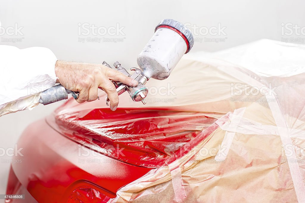 auto engineer paiting a red paint on  car stock photo