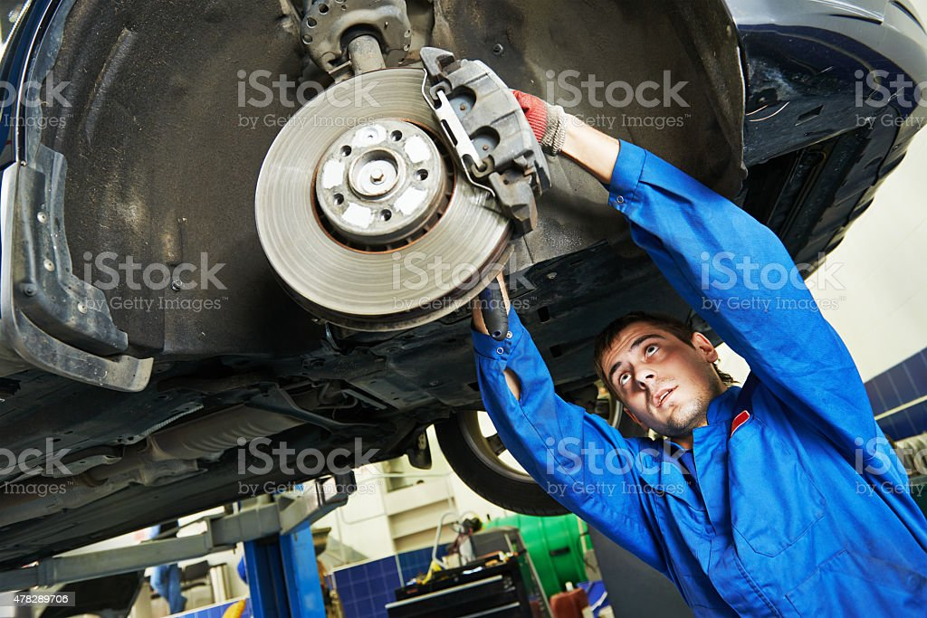 auto mechanic at car brake shoes examining stock photo
