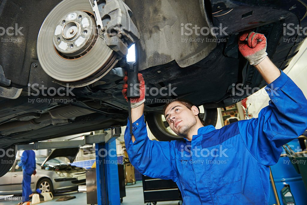 auto mechanic at car brake shoes eximining stock photo