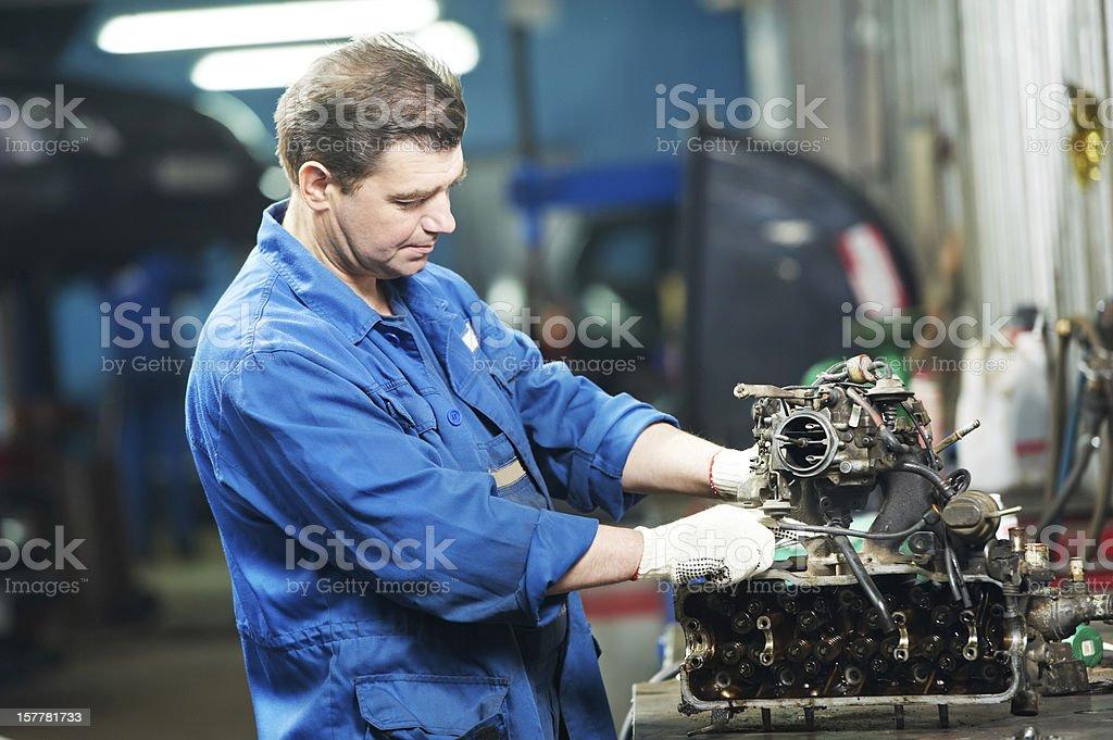 auto mechanic at repair work with engine stock photo