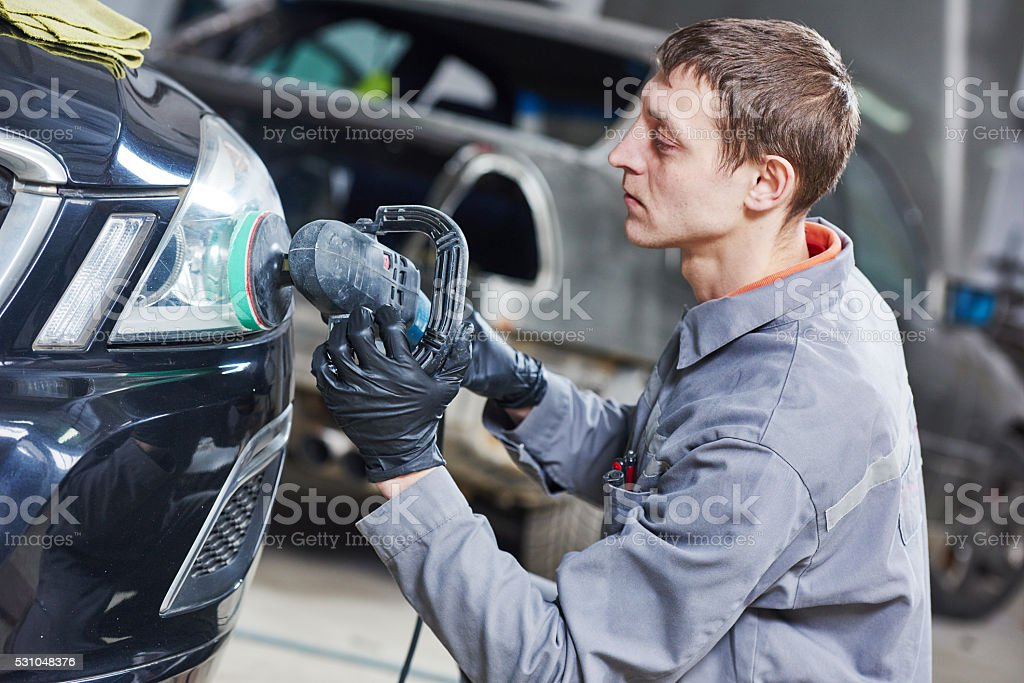 auto mechanic buffing and polishing car headlight stock photo