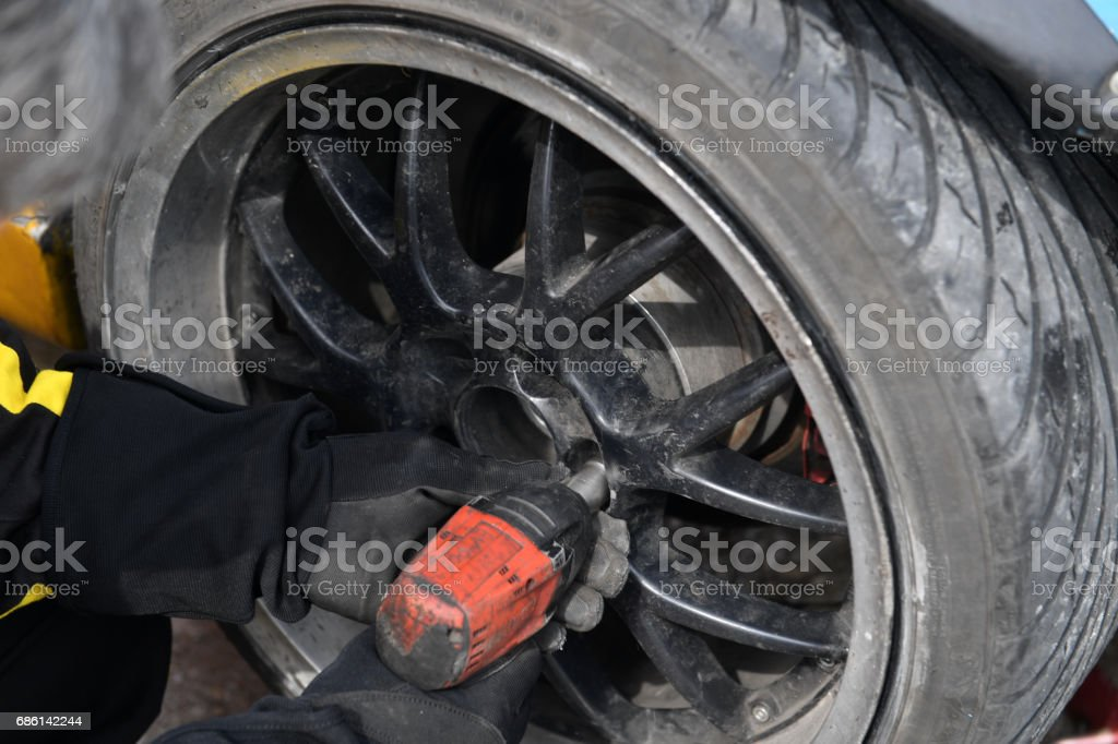 Auto mechanic changing a tyre stock photo