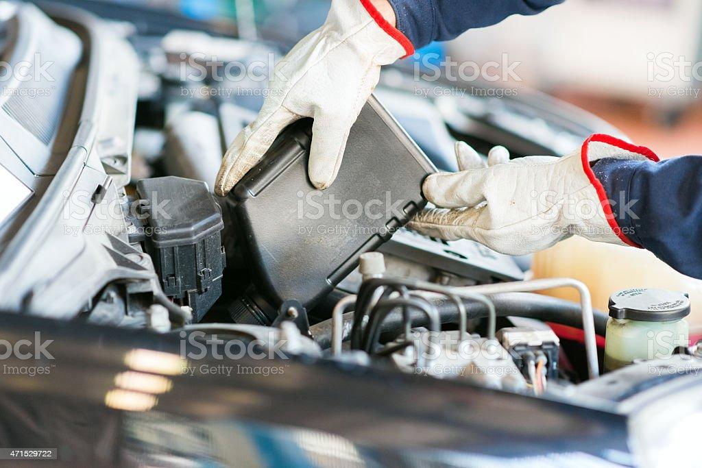 Auto mechanic changing motor oil stock photo