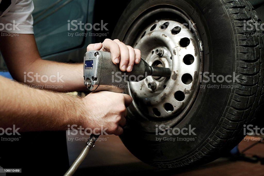Auto mechanic changing wheel stock photo