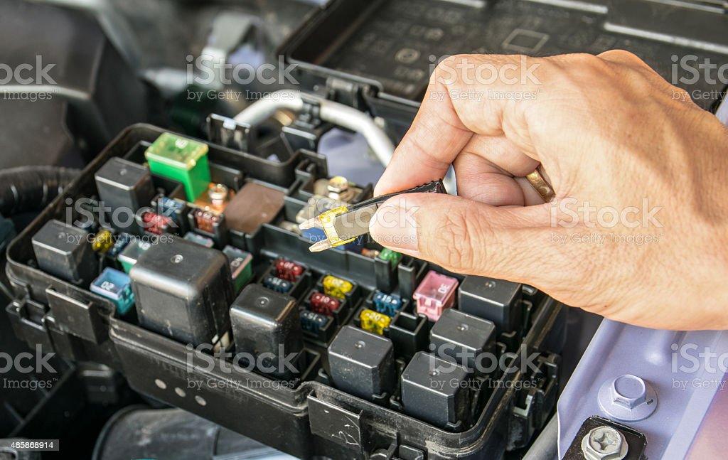 Auto mechanic checking a car fuse stock photo