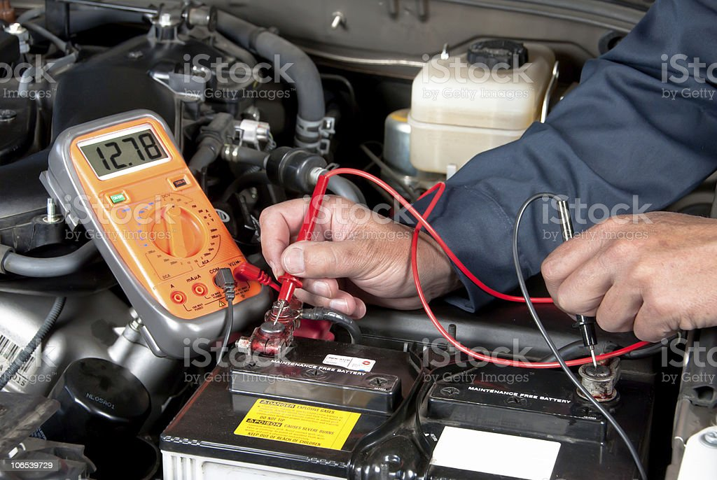 Auto mechanic checking car battery voltage stock photo