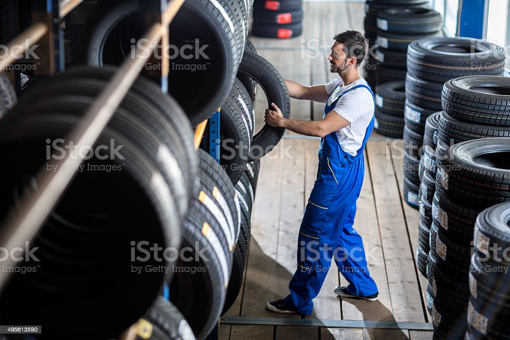 Auto mechanic  choose tire for car stock photo