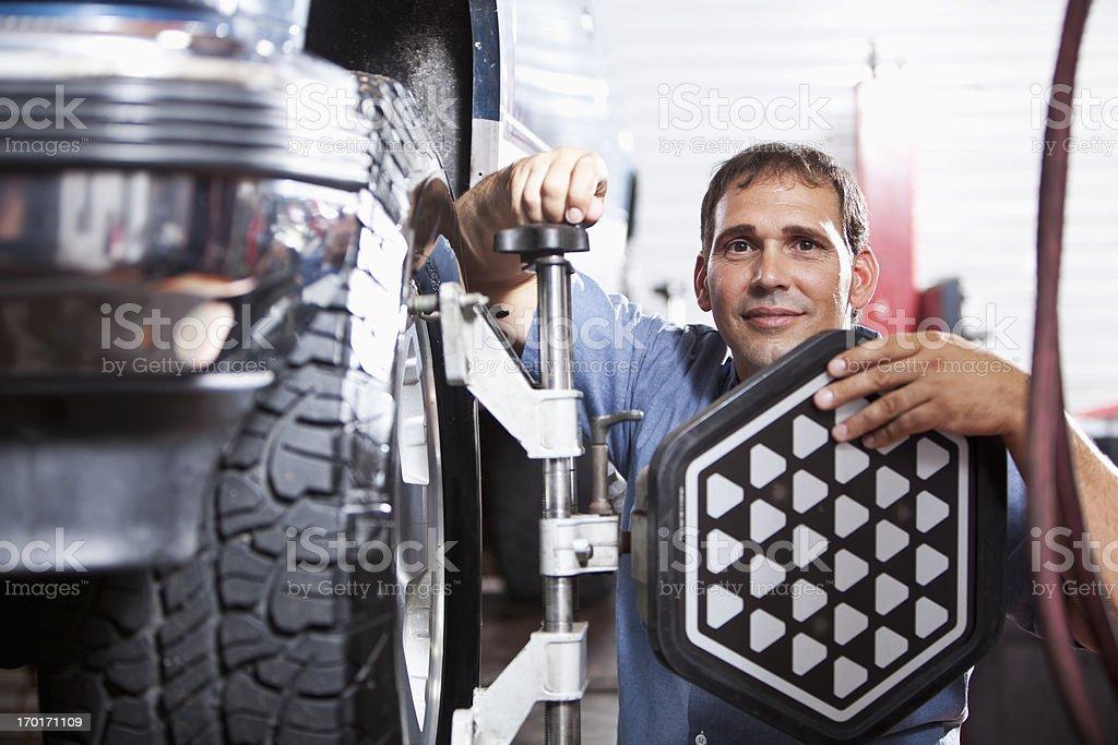 Auto mechanic doing wheel alignment royalty-free stock photo