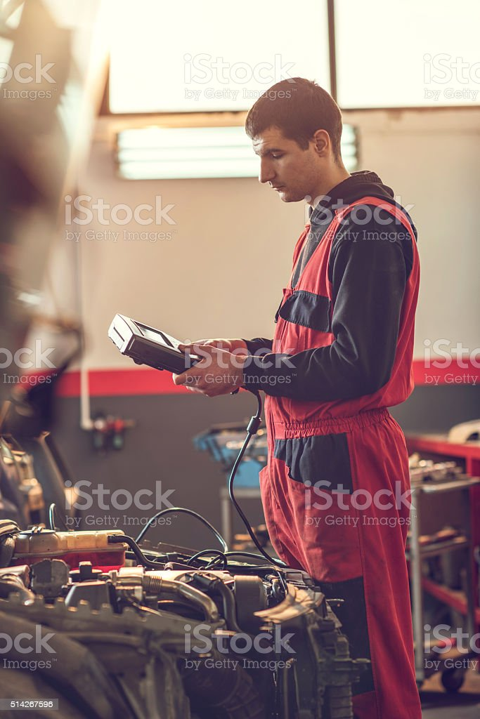 Auto mechanic examining a car engine with voltmeter. stock photo