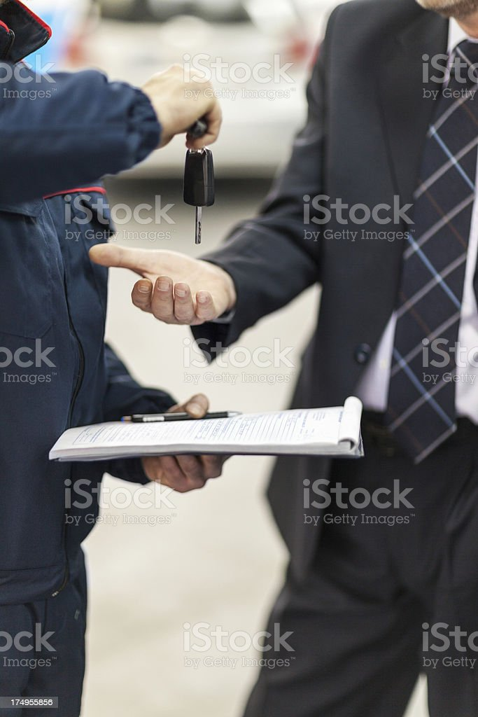 Auto mechanic giving car keys to client royalty-free stock photo