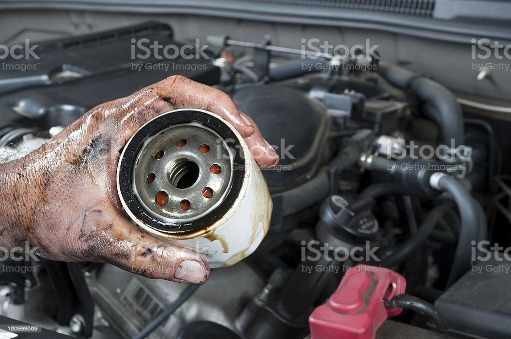 Auto mechanic holding oil filter royalty-free stock photo