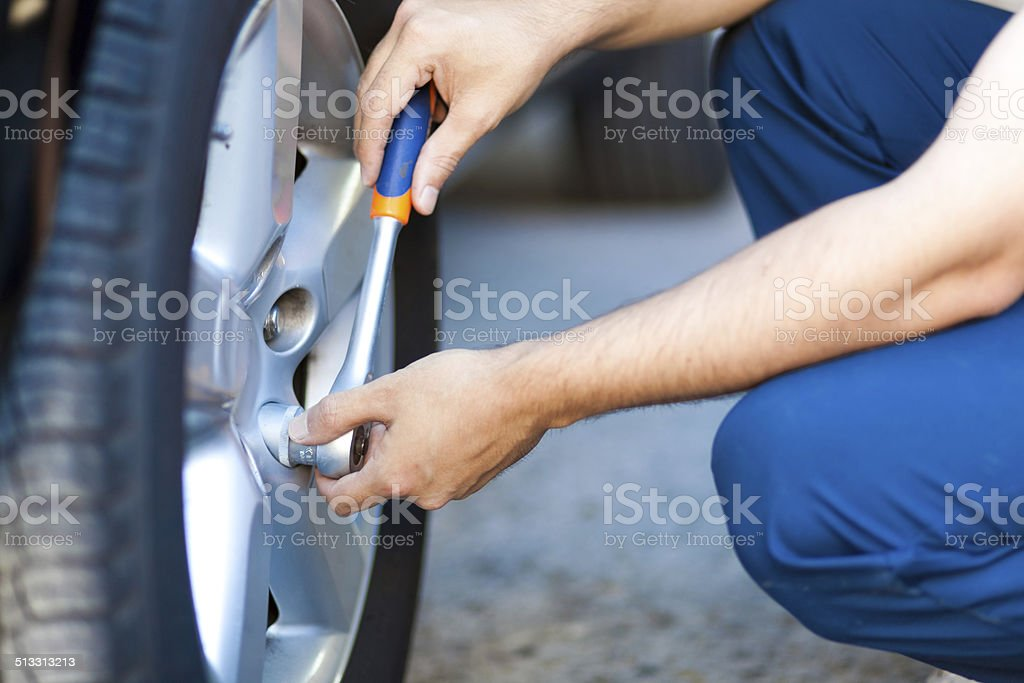 Auto mechanic in his workshop changing tires or rims stock photo
