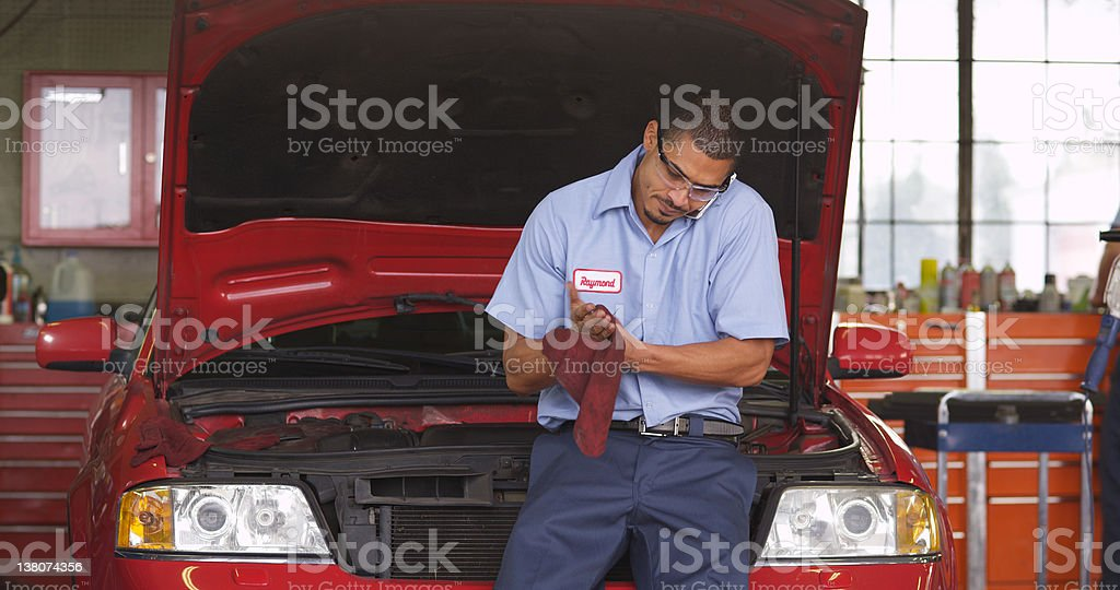 Auto mechanic in repair shop on cell phone royalty-free stock photo