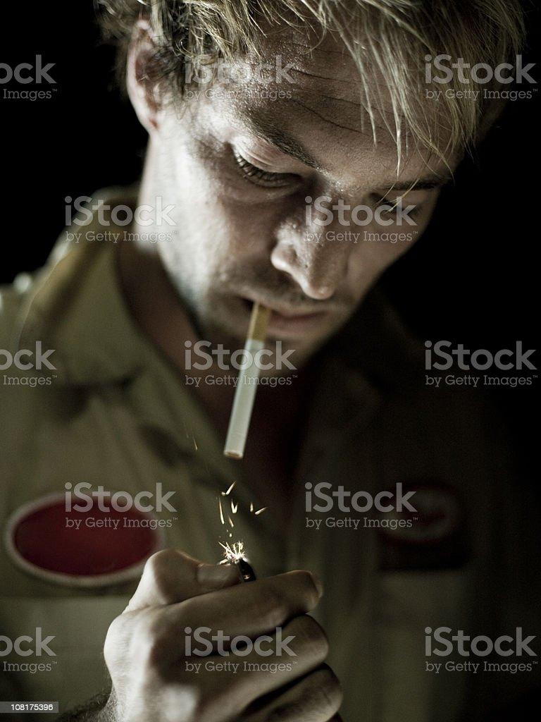 Auto Mechanic Lighting a Cigarette stock photo
