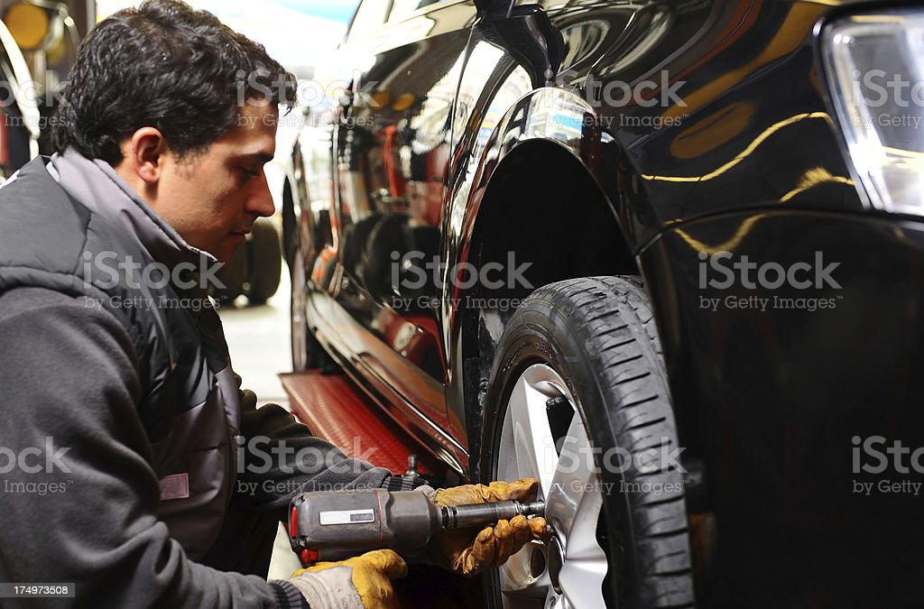 Auto mechanic replace tire. Air impact tool royalty-free stock photo
