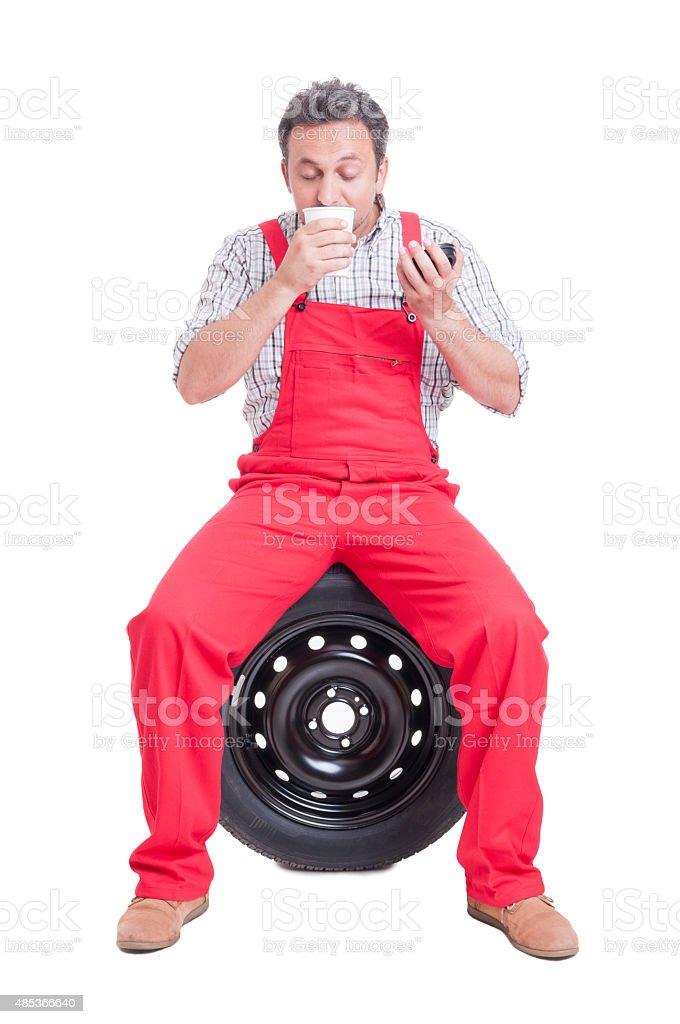 Auto mechanic smelling fresh coffee stock photo