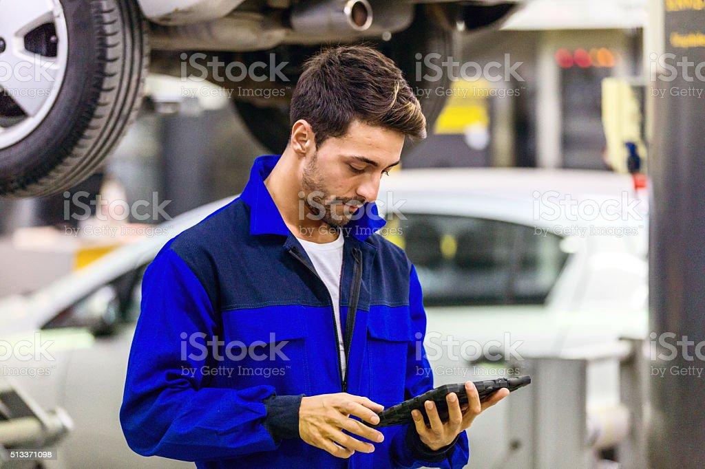 Auto Mechanic Using Digital Tablet stock photo