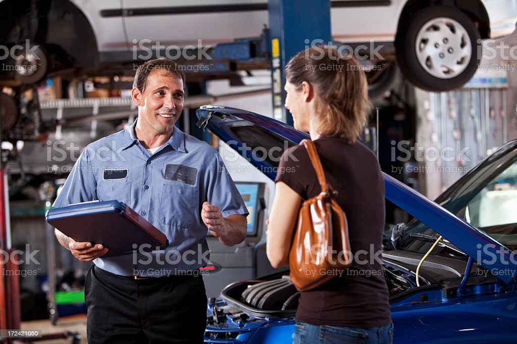 Auto mechanic with customer royalty-free stock photo