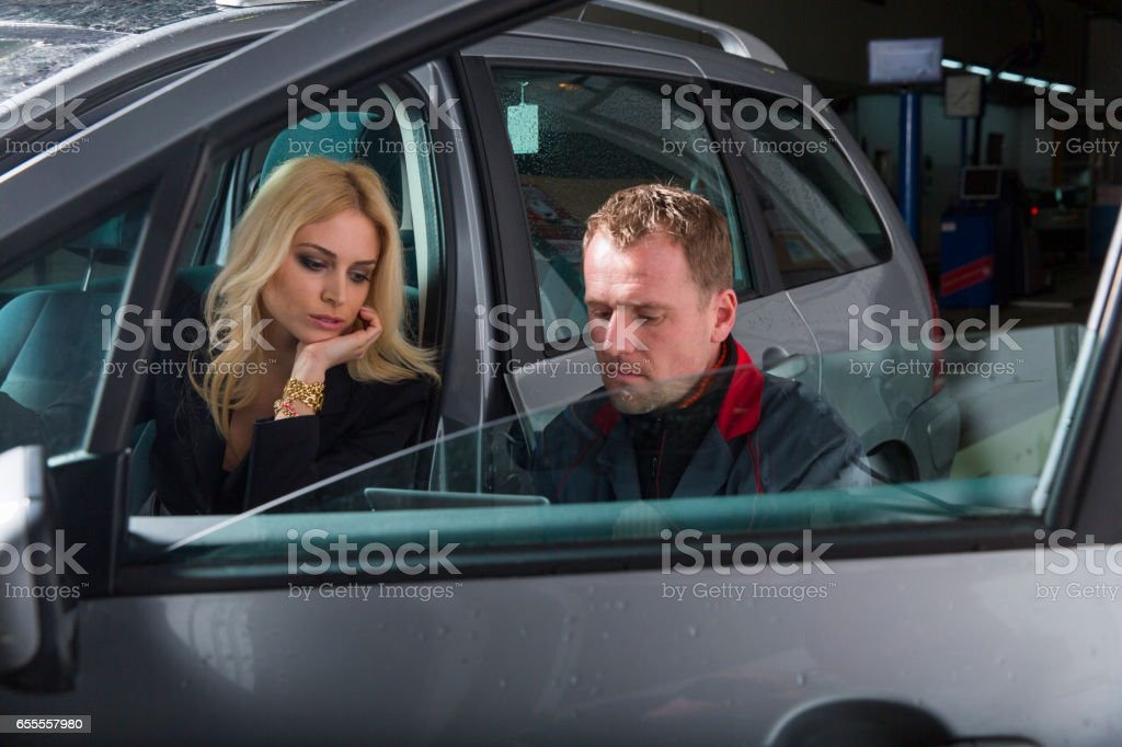 Auto mechanic with digital tablet talking to a cute customer. stock photo
