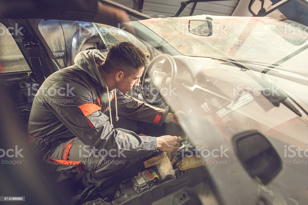 Auto mechanic working inside of a car in repair shop. stock photo