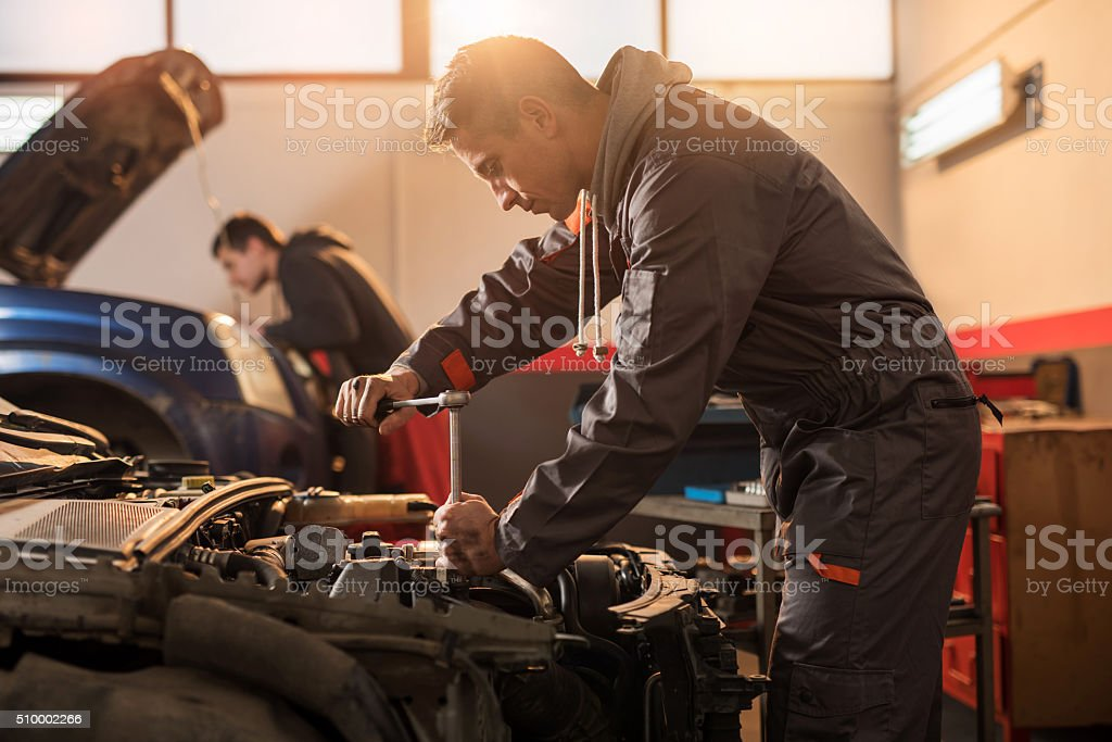 Auto mechanic working on a car engine in repair shop. stock photo