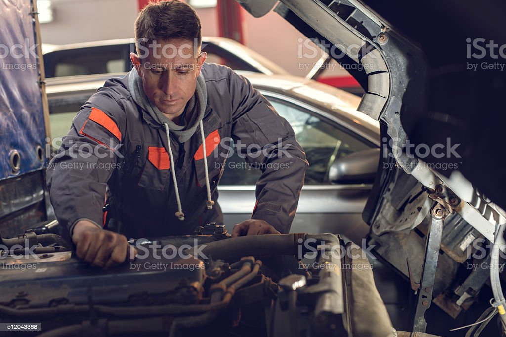 Auto mechanic working on a truck in a repair shop. stock photo