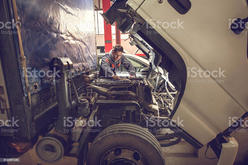 Auto mechanic working on a truck in auto repair shop. stock photo