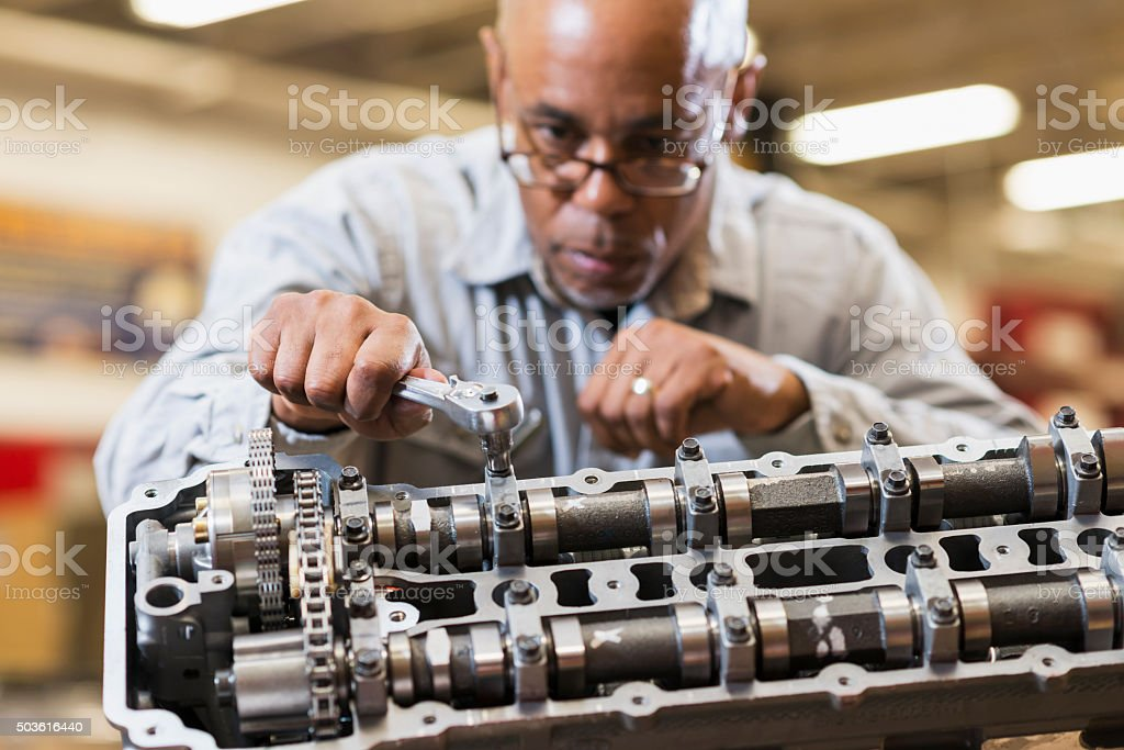 Auto mechanic working on gasoline engine stock photo