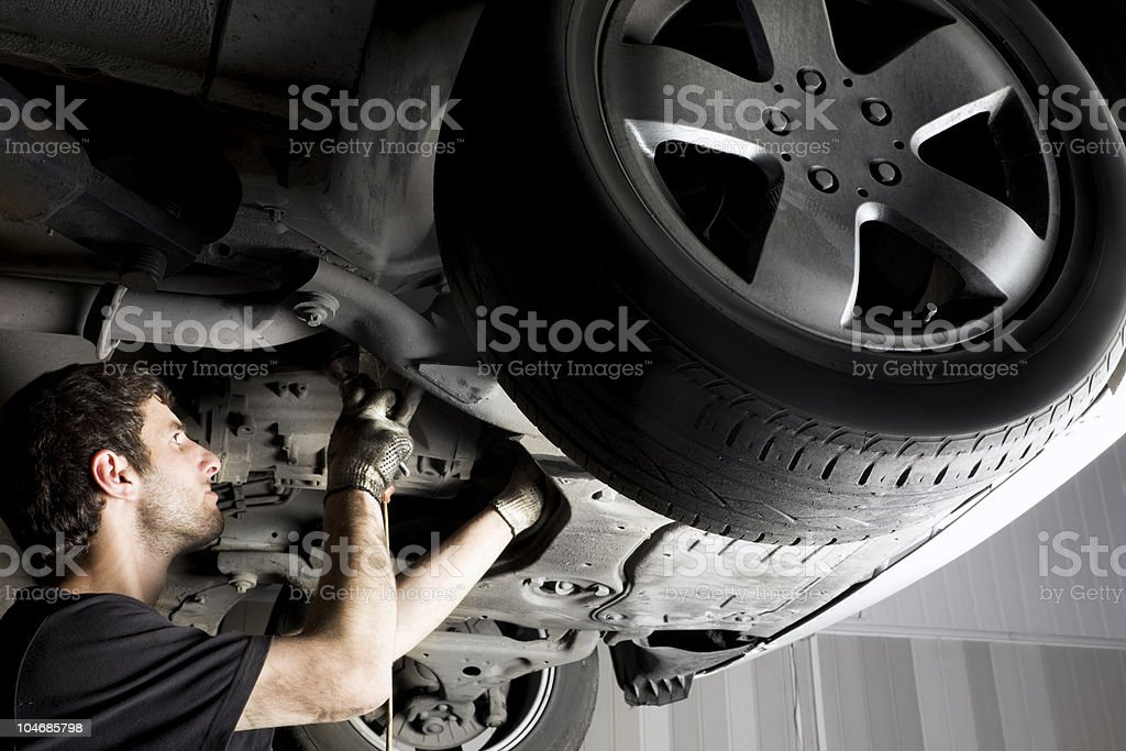 Auto mechanic working under the car stock photo