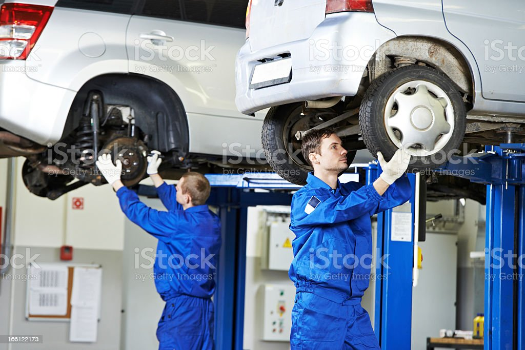 Auto mechanics working on car suspension stock photo