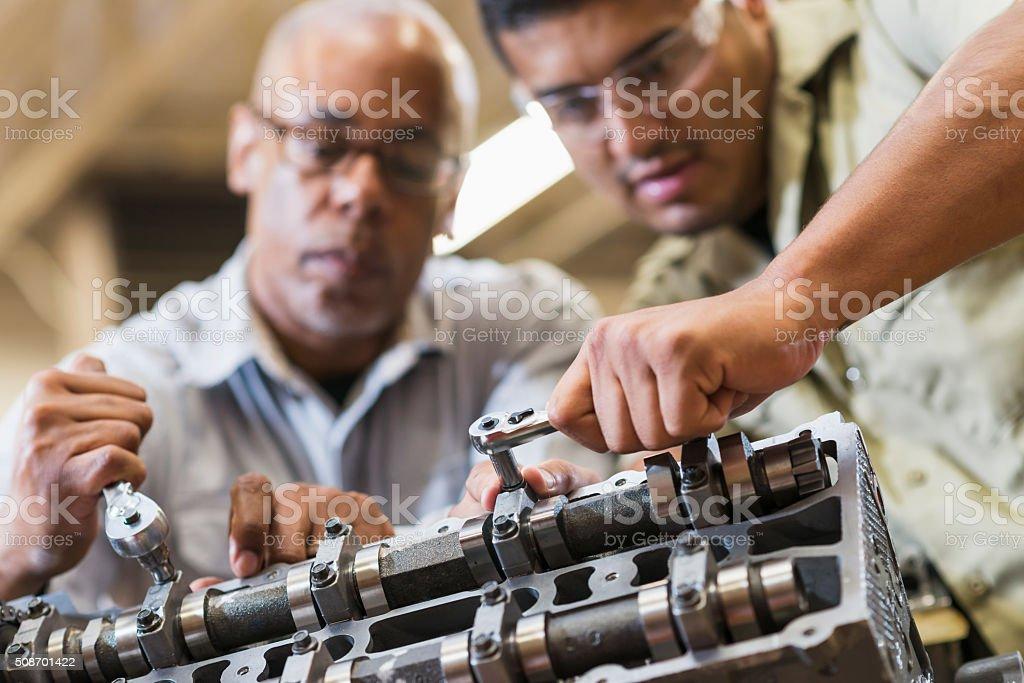 Auto mechanics working on gasoline engine stock photo