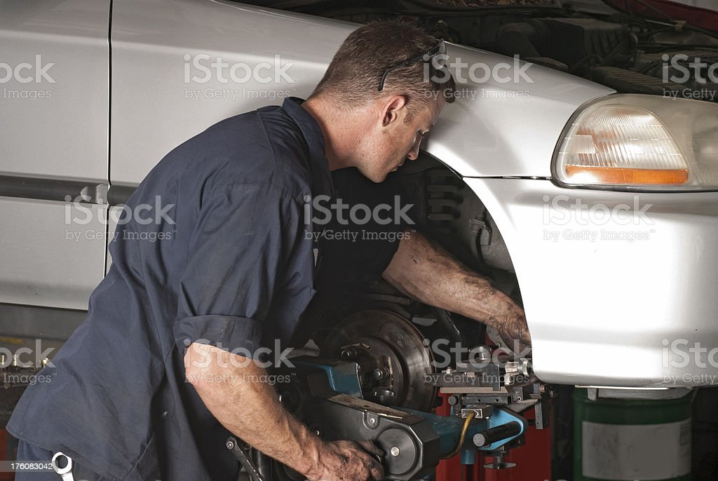 Auto Repair Mechanic Working on Brakes royalty-free stock photo