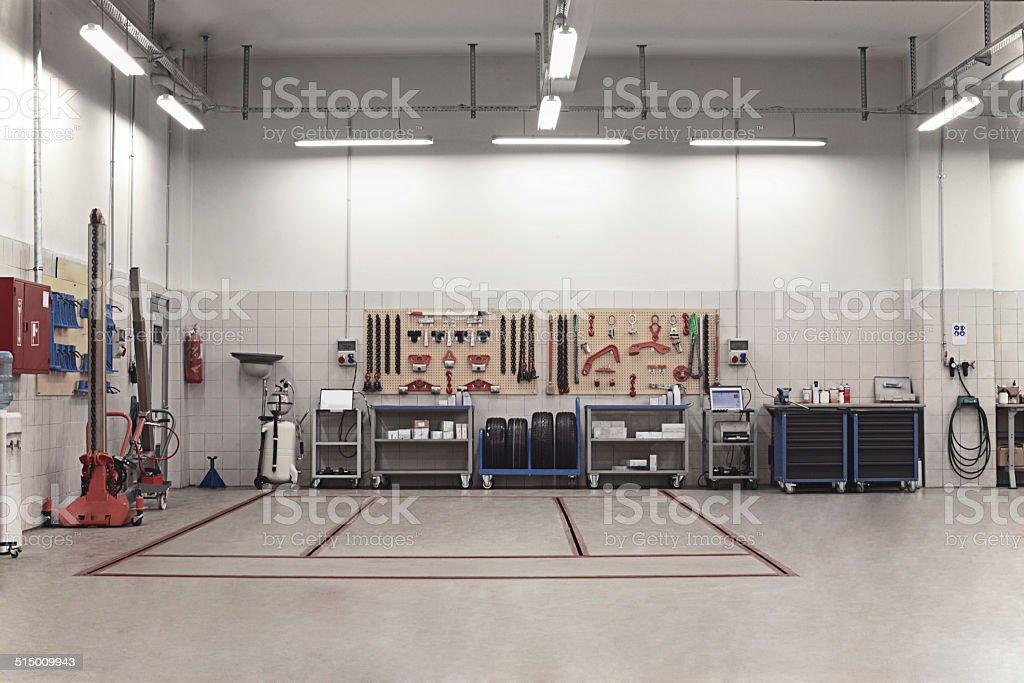 Auto repair shop interior with mechanic in background for Auto interieur reinigen amsterdam