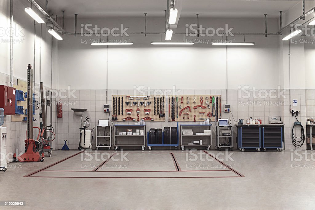 Auto Repair Shop Interior with Mechanic in Background stock photo