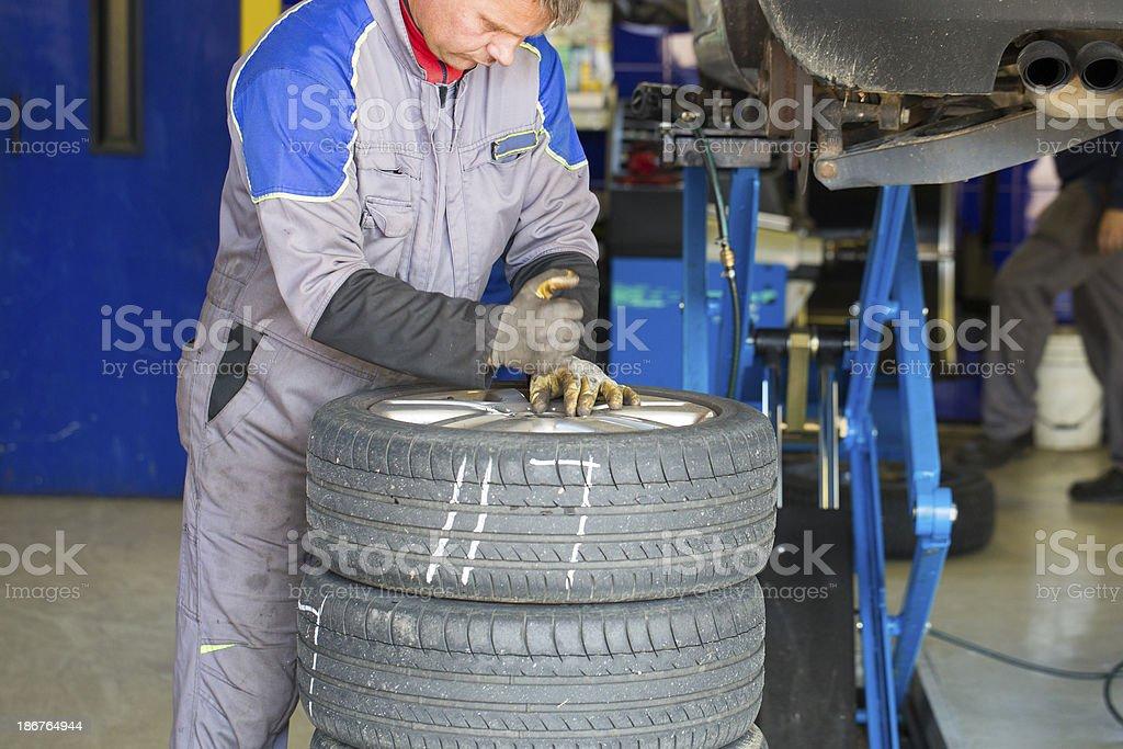 Auto repar shop...worker is prepairing tires for winter stock photo