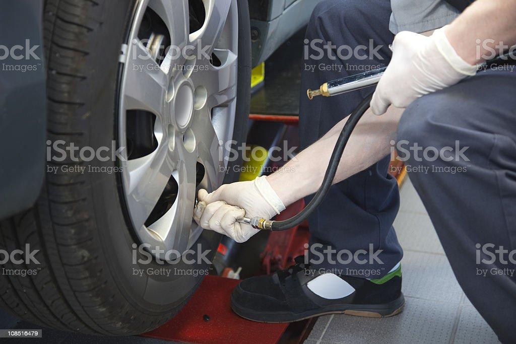 Auto Service Technician Checking Tire Pressure royalty-free stock photo