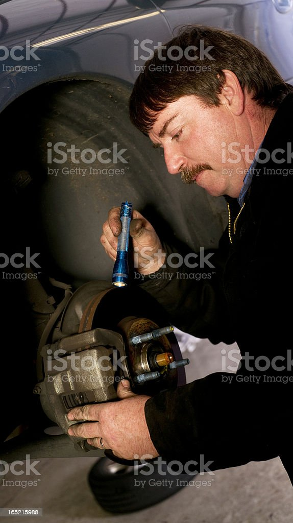 Auto Technician Mechanic Checks Rotors on Car Braking System royalty-free stock photo