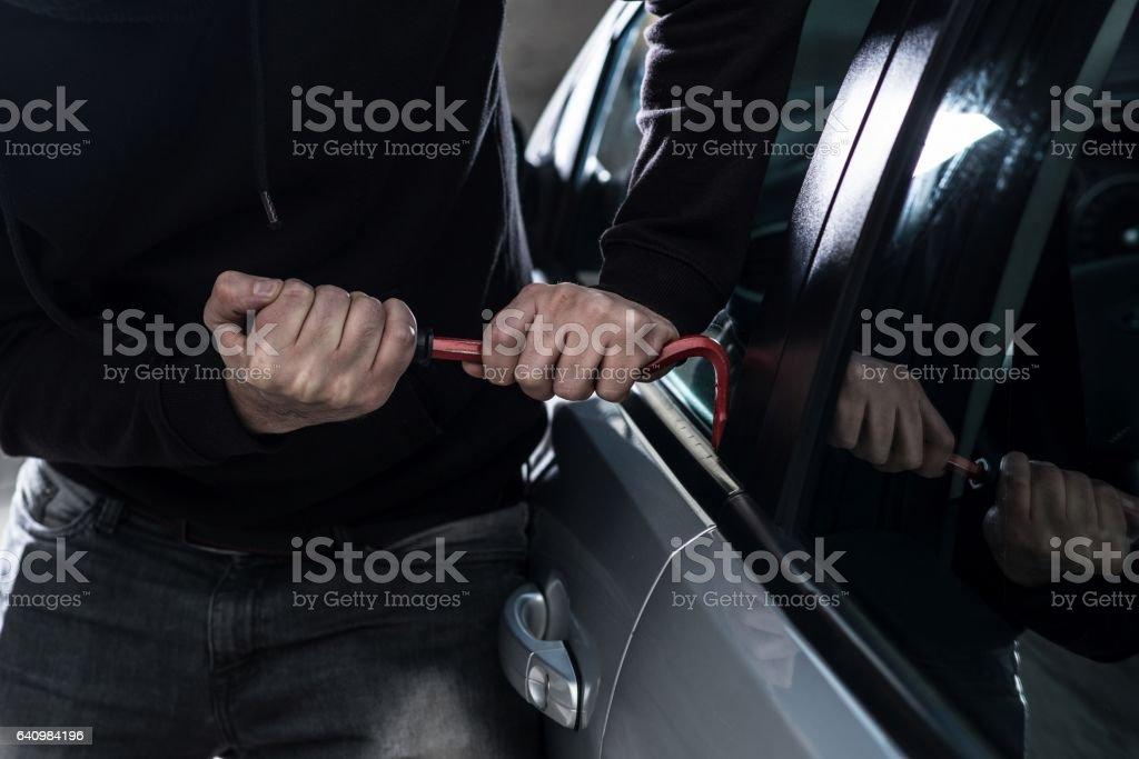 Auto thief in black balaclava trying to break into car stock photo