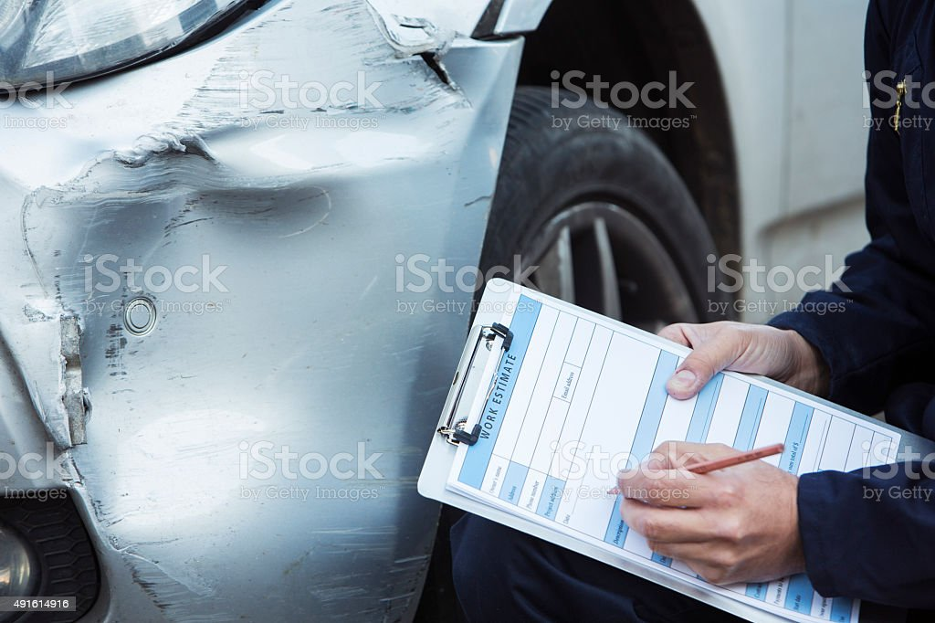 Auto Workshop Mechanic Inspecting Damage To Car stock photo