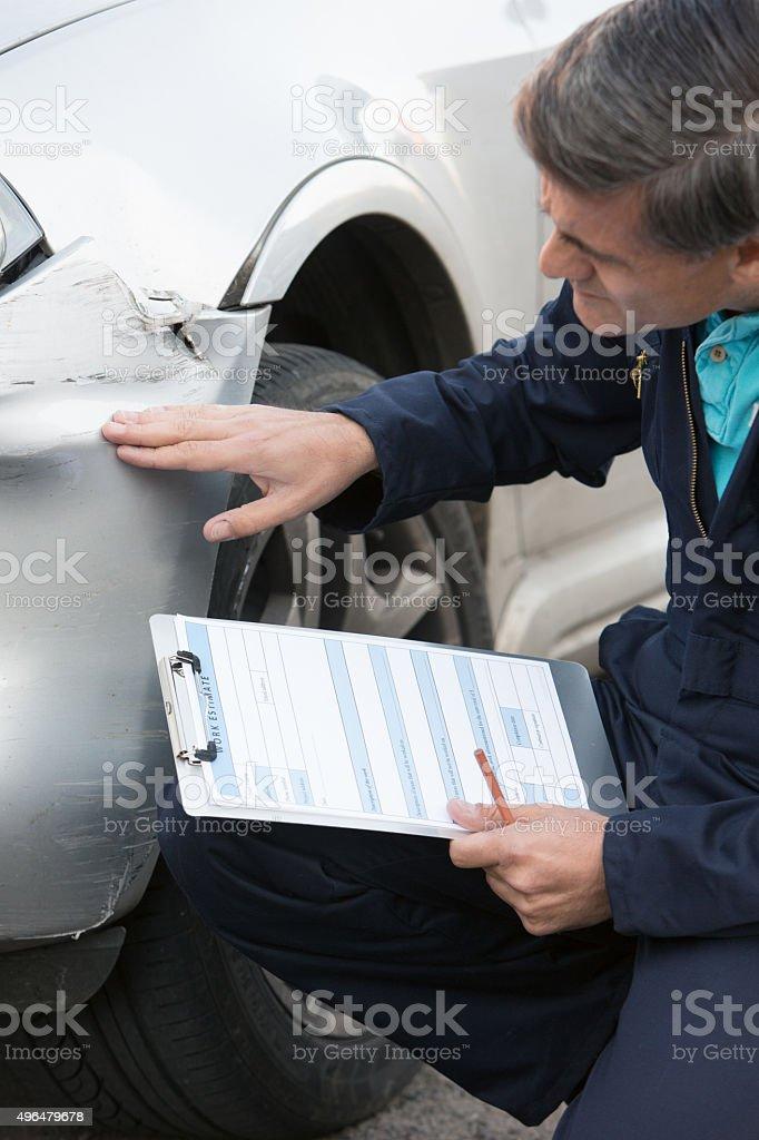Auto Workshop Mechanic Inspecting Damage To Car stock photo