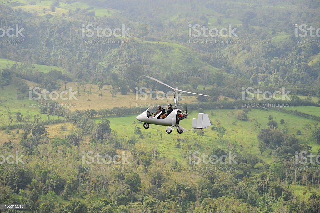 Autogyro flying above the tropical landscape royalty-free stock photo