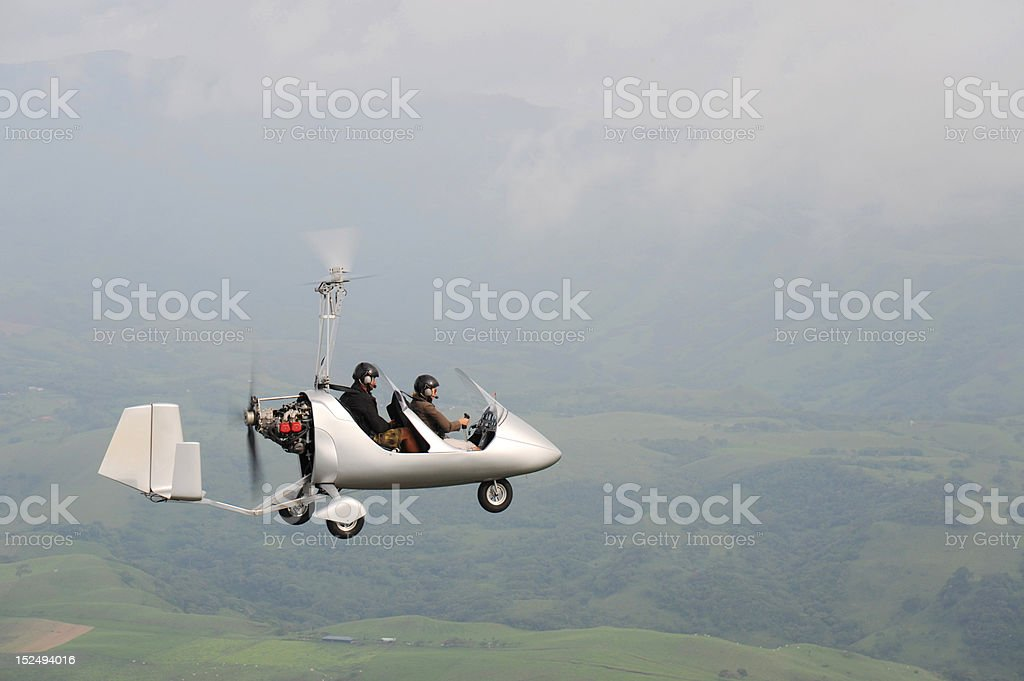 Autogyro flying over the tropical landscape royalty-free stock photo