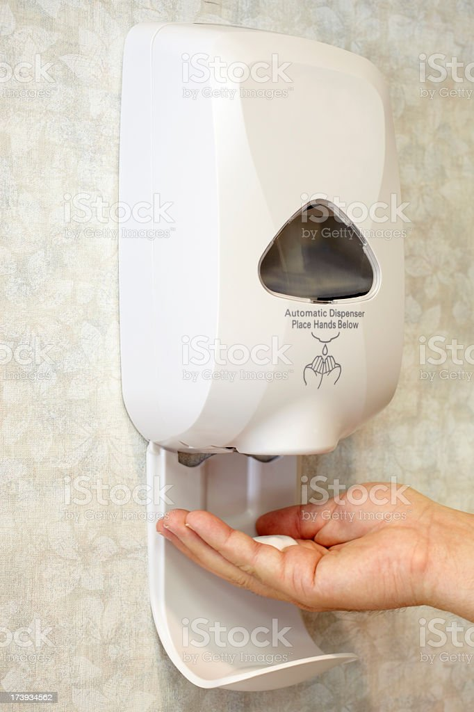 Automated from soap dispenser with hand underneath stock photo