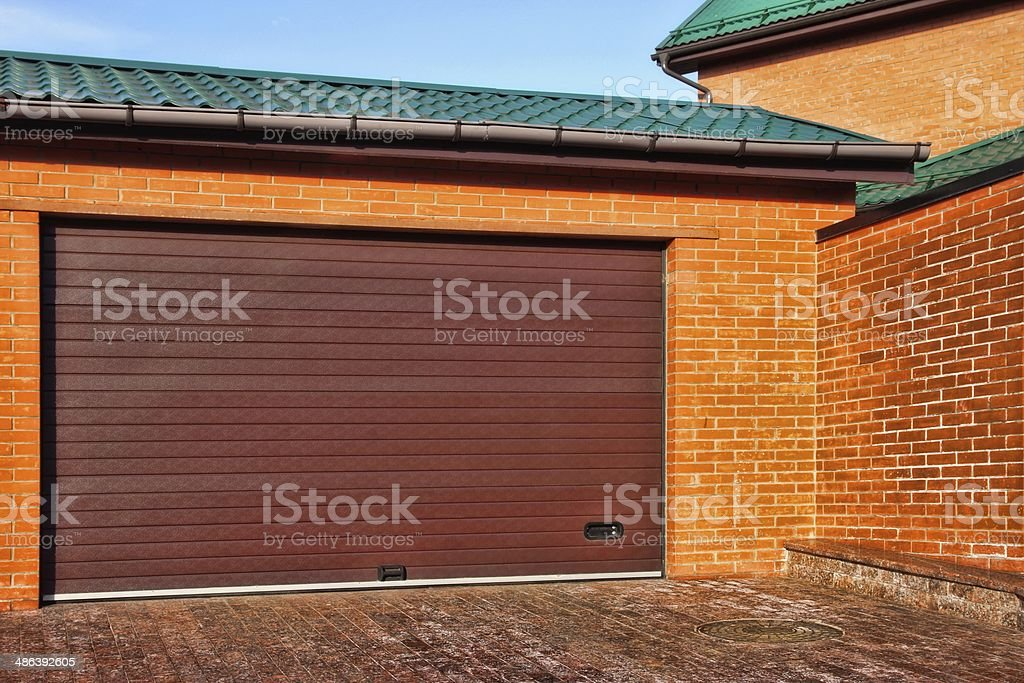 Automatic Garage Gate and Single Red House with brick wall, stock photo