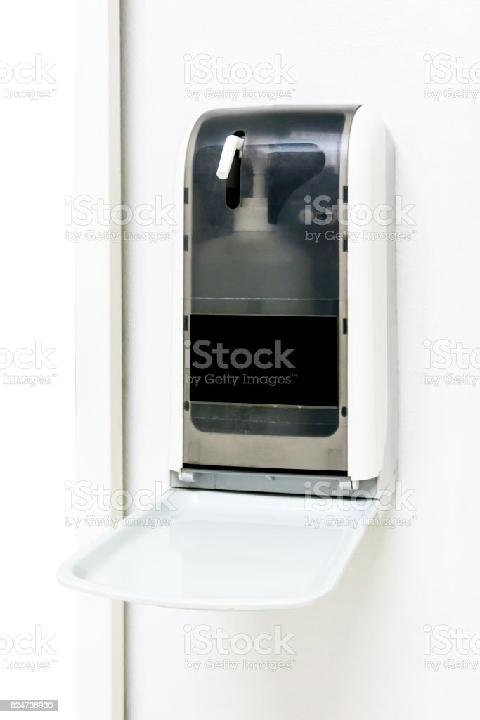 Automatic hand sanitize dispenser on white wall stock photo