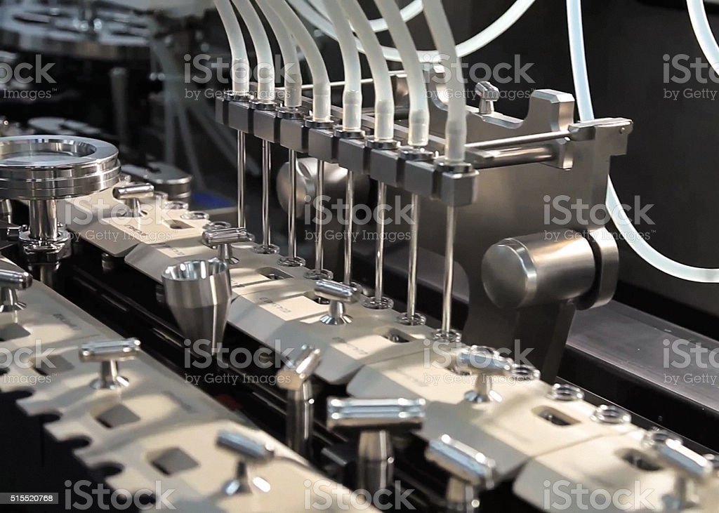 Automatic line for filling bottles of drugs. stock photo