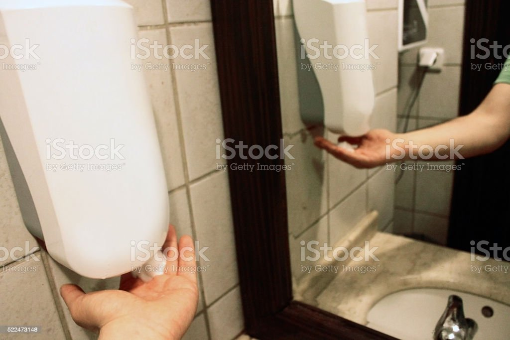 Automatic liquid soap dispenser with hand stock photo