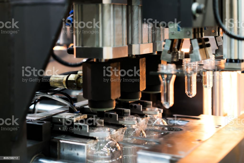 Automatic PET/ Plastic bottle blow moulding machine working in factory. stock photo
