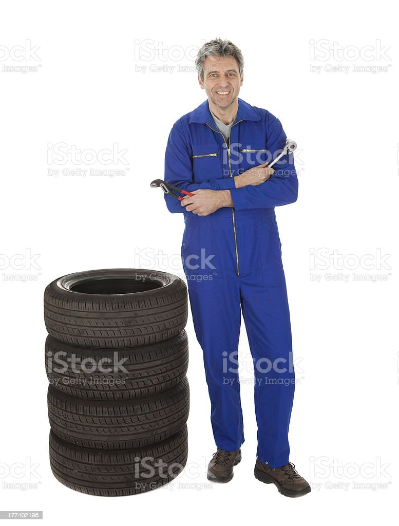 Automechanic standing next to car tires royalty-free stock photo