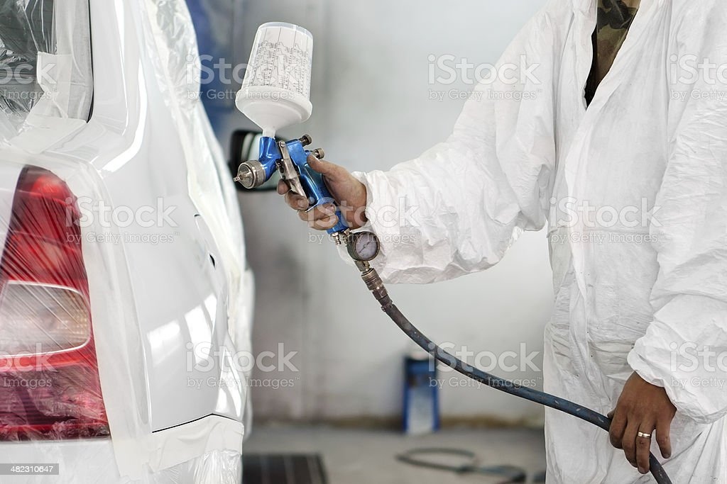 automobile engineer spraying paint on a white car stock photo